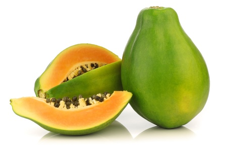 fresh papaya fruit and a cut one on a white background