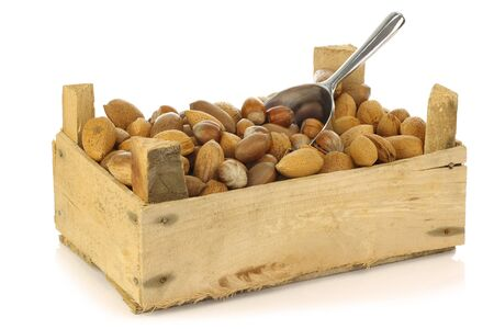 assorted nuts in a wooden box with an aluminum scoop on a white background  photo