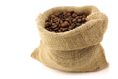 coffee beans in a burlap bag on a white background  Фото со стока