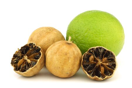cut dried  white lime  fruit and a fresh one on a white background photo