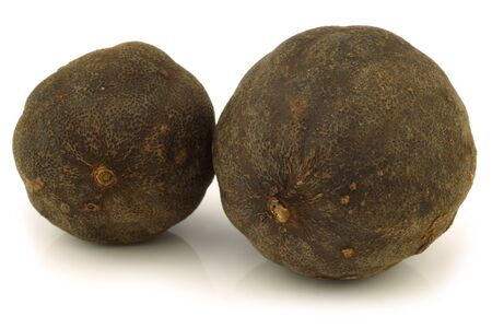 dried  black lime fruit on a white background  photo