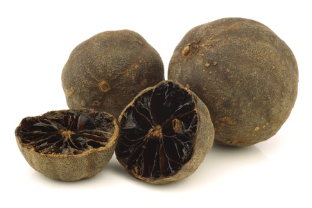 dried  black lime fruit and a cut one on a white background  photo