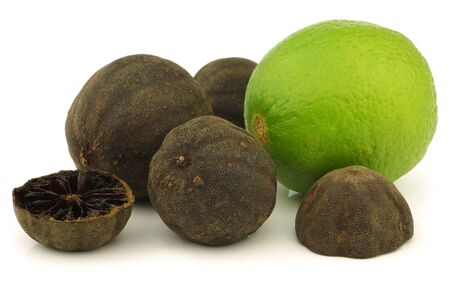 cut dried  black lime fruit and a fresh one on a white background  photo