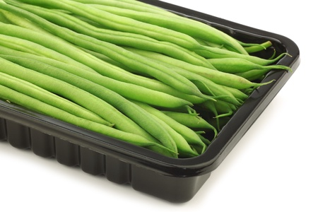 haricot vert: small and slender green beans  haricot vert  in a black plastic container on a white background