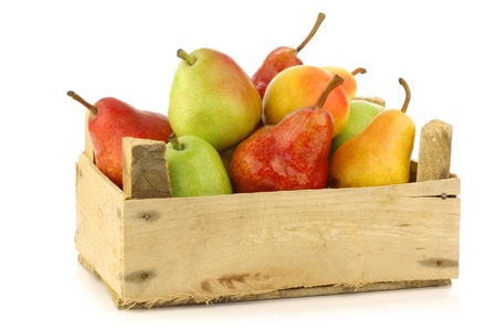 Assortment of different colorful pears in a wooden crate on a white background  版權商用圖片