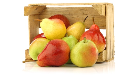 Assortment of different colorful pears in a wooden crate on a white background  photo