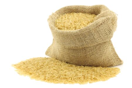unpolished rice  whole grain  in a burlap bag on a white background  Stock Photo - 15109481