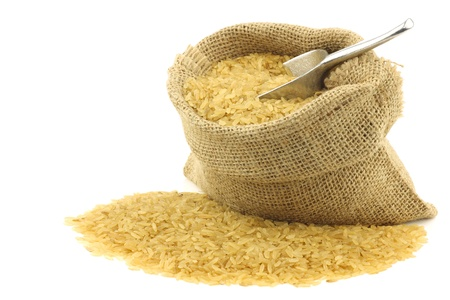unpolished: unpolished rice  whole grain  in a burlap bag with an aluminum scoop on a white background  Stock Photo