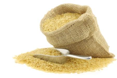 arroz blanco: grano de arroz sin pulir todo en una bolsa de arpillera con una cuchara de aluminio sobre un fondo blanco
