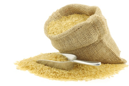 unpolished rice  whole grain  in a burlap bag with an aluminum scoop on a white background  photo