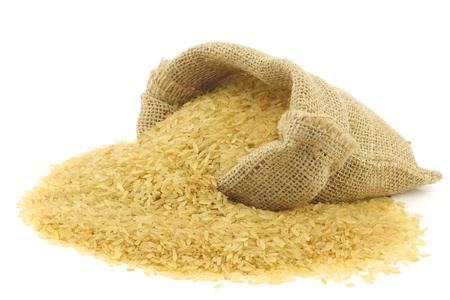 unpolished rice  whole grain  in a burlap bag on a white background  photo