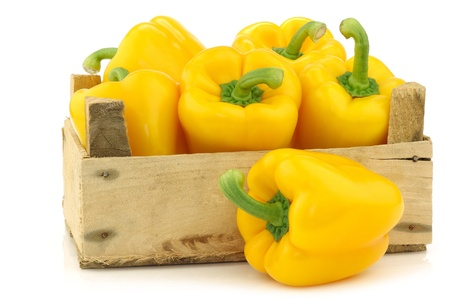 fresh yellow bell peppers  capsicum  a in a wooden crate on a white background