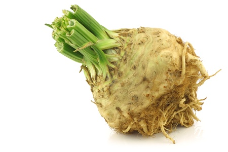 fresh celery root with some foliage on a white background