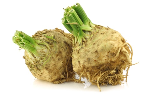 fresh celery roots with some foliage on a white background