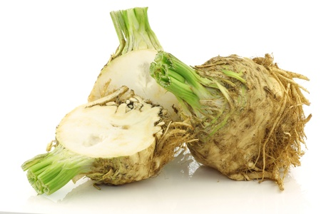 freshly harvested celery root and a cut one on a white background