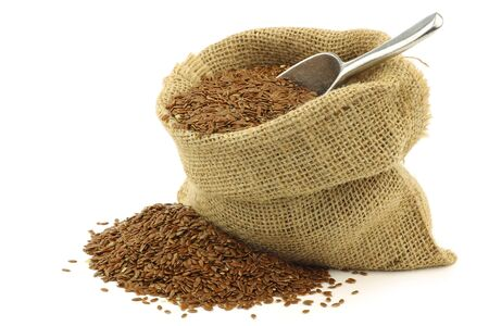 Flax seed  linseed  in a burlap bag with an aluminum scoop on a white background Stock Photo - 15109478