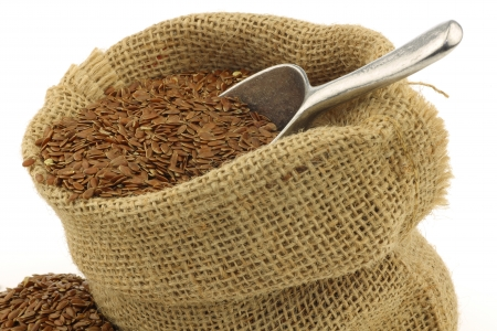 Flax seed  linseed  in a burlap bag with an aluminum scoop on a white background Stock Photo - 15109799