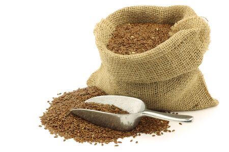 flax seed oil: Flax seed  linseed  in a burlap bag with an aluminum scoop on a white background