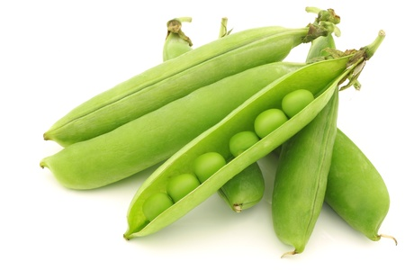 opened green pea pods with peas visible on a white background