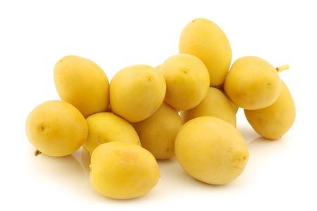 dactylifera: freshly harvested branch with dates  Phoenix dactylifera  on a white background Stock Photo