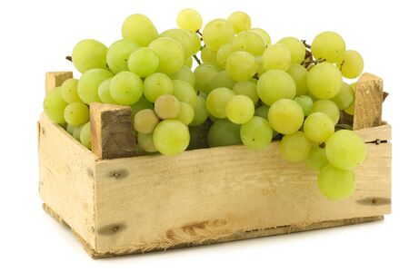 seedless: fresh white seedless grapes on the vine in a wooden crate on a white background