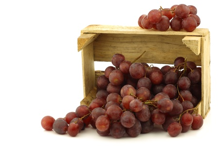 seedless: fresh red seedless grapes on the vine in a wooden crate on a white background Stock Photo
