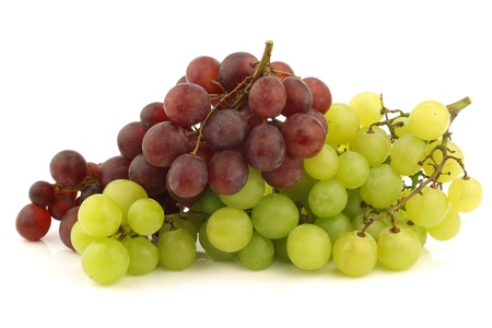 seedless: fresh red and white seedless  grapes on the vine on a white background