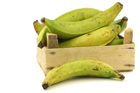 unripe baking bananas  plantain bananas  in a wooden crate on a white background Banque d'images