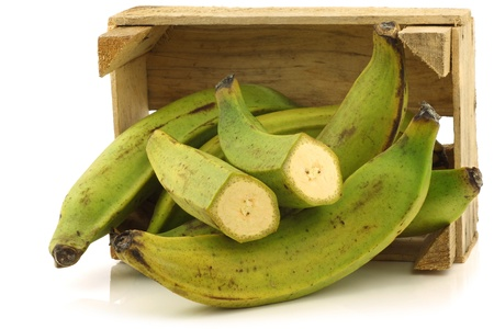 unripe baking bananas  plantain bananas  and a cut one  in a wooden crate on a white background