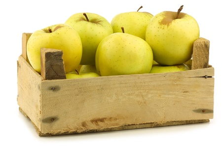 golden apple: fresh  Golden Delicious  apples in a wooden crate  on a white background Stock Photo