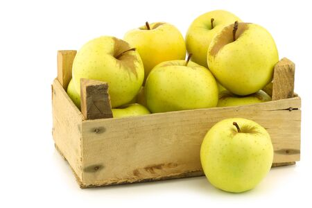 fresh  Golden Delicious  apples in a wooden crate  on a white background Фото со стока
