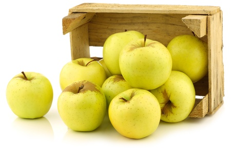 fresh  Golden Delicious  apples in a wooden crate  on a white background Banque d'images