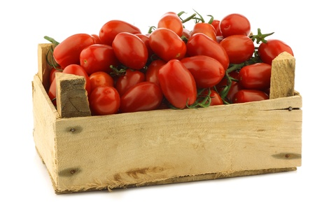 fresh italian cherry tomatoes on the vine in a wooden crate on a white background photo