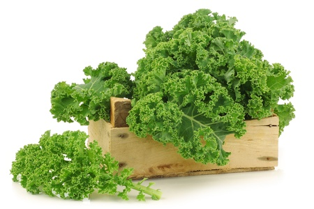 freshly harvested  kale cabbage in a wooden crate on a white background photo