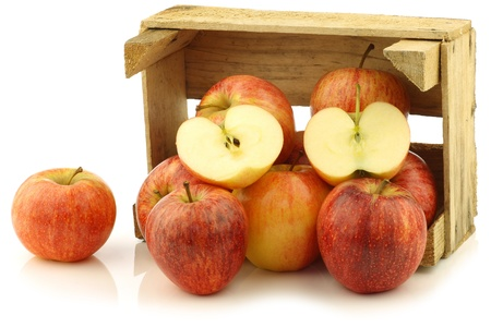 fresh  royal gala  apples and a cut one in a wooden crate on a white background photo