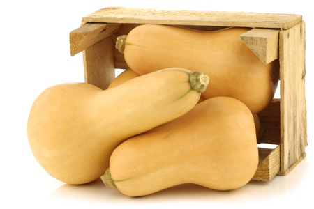 butternut: bottle shaped butternut pumpkins in a wooden crate on a white background
