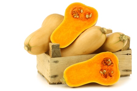 butternut: bottle shaped butternut pumpkins and two halves in a wooden crate on a white background Stock Photo