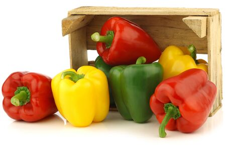 red,yellow and green bell peppers  capsicum  in a wooden crate on a white background