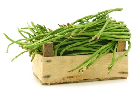 frijoles: habas frescas largas Vigna unguiculata subsp sesquipedalis en una caja de madera sobre un fondo blanco Foto de archivo