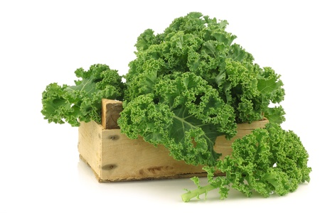 freshly harvested  kale cabbage in a wooden crate on a white background