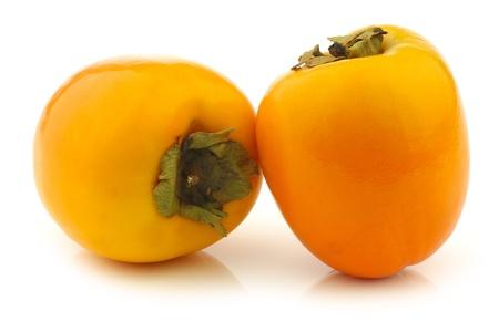 asian produce: two fresh kaki fruits on a white background