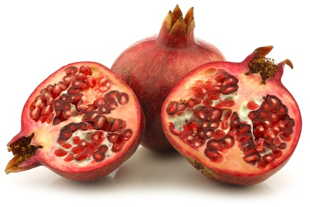 punica granatum: one whole pomegranate  Punica granatum  and two halves on a white background Stock Photo