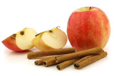 cannelle: dried cinnamon sticks, a fresh apple and some cut pieces on a white background