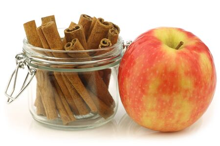 cannelle: dried cinnamon sticks in a glass jar and a fresh apple on a white background