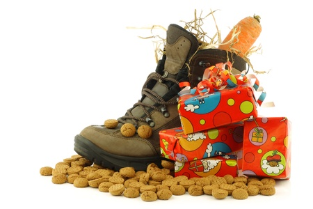 shoe with a winter carrot and some straw set for  Sinterklaas  and some presents on a white background