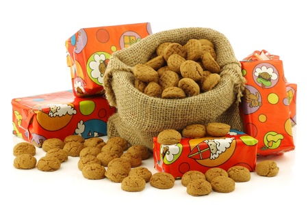 bunch of Dutch  pepernoten  eaten at Dutch festivities around december 5th called  Sinterklaas  in a burlap bag and an aluminum scoop on a white background