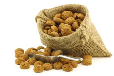 bunch of Dutch  pepernoten  eaten at Dutch festivities around december 5th called  Sinterklaas  in a burlap bag and an aluminum scoop on a white background Stock Photo - 16643368