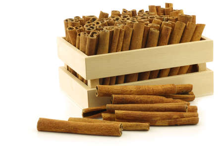 cannelle: dried cinnamon sticks in a wooden box on a white background