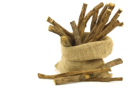 licorice root sticks in a burlap bag on white background Stock Photo