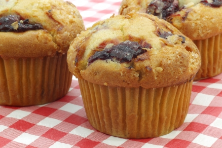 freshly baked cherry muffins on a red and white checkered table cloth photo